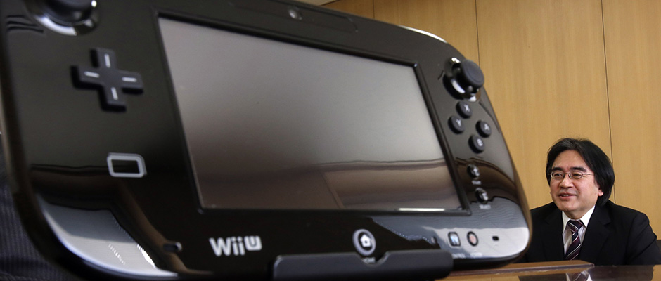 Nintendo Co's President Satoru Iwata speaks next to company's Wii U game controller during an interview with Reuters at the company headquarters in Kyoto, western Japan