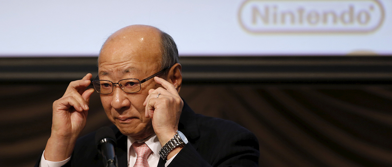 Nintendo Co Chief Executive Kimishima adjusts his glasses during a news conference in Tokyo
